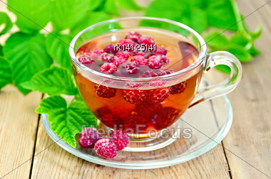 Tea With Raspberries In A Glass Cup, Green Raspberry Leaves On The Background Of Wooden Boards Stock Photo