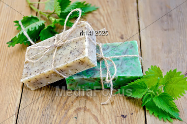 Two Bars Of Homemade Soap, Tied With Twine, Nettle On The Background Of Wooden Boards Stock Photo