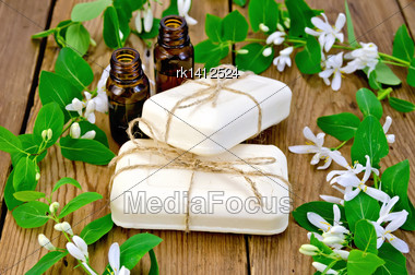 Two Bottles Of Aromatic Oil, Two Bars Of White Soap, Twigs With Leaves And White Flowers Of Honeysuckle On A Background Of Wooden Boards Stock Photo