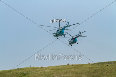 Two Military Helicopters On Maneuvers, Protect Troops Stock Photo