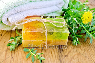 Two Pieces Of Homemade Soap, Tied With Twine With Rhodiola Rosea Flowers On A Background Of Wooden Boards Stock Photo