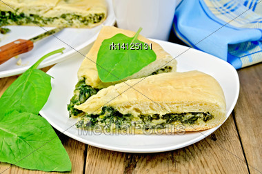 Two Pieces Of Pie With Spinach And Cheese On A Plate, Spinach Leaves, Knife, Napkin On The Background Of Wooden Boards Stock Photo
