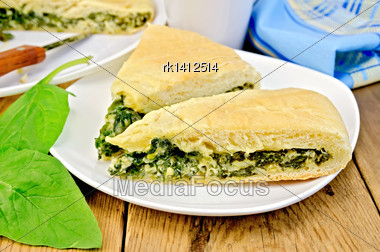 Two Pieces Of Pie With Spinach And Cheese On A Plate, Spinach Leaves, Cup, Knife, Napkin On Wooden Board Stock Photo