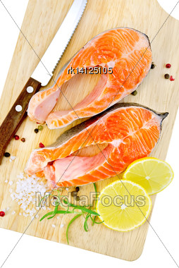 Two Pieces Of Trout With Rosemary, Lemon And Coarse Salt, A Knife On A Wooden Board Isolated On White Background Stock Photo