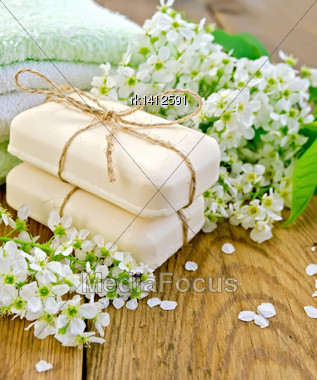 Two Pieces Of White Soap, Flowers, Bird Cherry, A Towel On The Background Of Wooden Boards Stock Photo