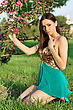Alluring Brunette Sitting On The Grass And Touching A Branch Of Flowering Tree