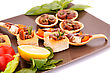 Anchovies In Pastries, Lemon, Tomato, Lettuce And Basil On Brown Plate stock photography