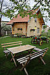 Antique Wooden Log Cabin, Table With Benches And An Old-fashioned Horse-drawn Wagon In The Courtyard Farmhouse