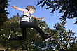 Atheletic Woman Wearing Fitness Clothing Leaping In A Wooded Area stock image