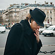 Attractive Bearded Man Wearing Hat Smoking On The Street In European City stock photography