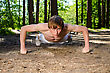 Attractive Man Doing A Push Up In Forest stock photo