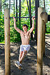 Attractive Man Pull-ups On A Bar In A Forest stock photo