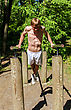 Attractive Man Pull-ups On A Bar In A Forest stock photography