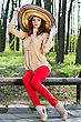 Attractive Young Brunette In Colorful Hat Sitting On The Bench