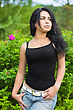 Attractive Young Woman In Black T-shirt Posing Near The Bushes