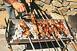 Barbecue On The Charcoal,man Hand Cuting The Meat.