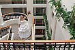 Balcony Beautiful Blonde Bride With Bunch Of Flowers In The Gallery stock photo