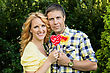 Beautiful Couple Holding Heart Shaped Red And Yellow Lollipops