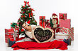 Beautiful Girl In Christmas Hat Surrounded By Holiday Accessories And New Year Tree