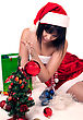 Beautiful Girl Wearing Christmas Hat Sitting On The Floor And Decorating New Year Tree