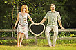Beautiful Married Couple Sitting Outside On Wooden Fence And Holding Heart Shaped Chalkboard stock photography