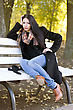 Beautiful Young Brunette Sitting On A Bench In Autumn Park