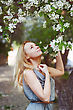 Beautiful Young Woman Is Enjoying By Spring Flowers. Wind, Freedom. Small Amount Of Grain Added For Best Final Impression stock photo