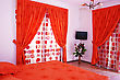 Bedroom With Red Curtains, Bedspread And Flowers.