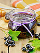 Black Currant Jam In A Glass Jar, Fresh Blackcurrant With Leaves, Napkin On A Wooden Board
