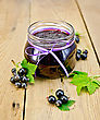 Black Currant Jam In A Glass Jar, Fresh Black Currant Berries With Leaves On A Wooden Board
