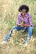 Leisure Black Woman Seated In High Grass Listening To Favorite Songs stock photo