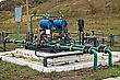 Blue Cylinders, Green With Red Edging Pipe Group Metering Device Of The Pipeline On The Black And White Based On The Background Of Yellow-green Grass And Bushes stock photo