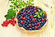 Blueberries With Red Currants In A Wicker Basket, A Sprig Of Blueberries And Red Currants With Green Leaves On A Light Wooden Board