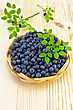 Blueberries In A Wicker Basket, Two Sprigs Of Blueberries With Green Leaves On A Light Wooden Board stock photo