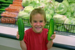 Boy at Grocery Store Holding Cucumbers stock photography