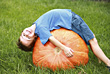 Boy Bending over on Pumpkin stock image