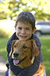 Boy Hugging Dog stock photography