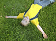 Playful Boy Laying in Grass with Arms Outstretched stock image