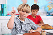 Boy Raising His Hand In Class stock photo