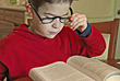 Boy reading with reading glasses on stock image
