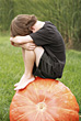 Thanksgiving Boy Thinking on top of Pumpkin stock image
