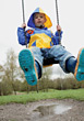 Boy Wearing A raincoat On A Swing stock photo