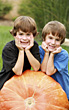 Thanksgiving Boys Leaning on a Pumpkin stock image
