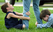 Boys Pulling on Persons Legs stock photography