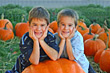 Children Boys Smiling Leaning on Huge Pumpkin stock photo