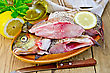 Bream Whole Peeled And Cut Into Chunks In A Clay Plate, Parsley, Lemon, Vegetable Oil, Napkin, Knife On The Background Of Wooden Boards