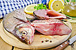 Bream Whole Peeled And Sliced Pieces On A Round Board, Parsley, Lemon, Vegetable Oil, Napkin, Knife On The Background Of Wooden Boards stock photography