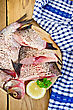 Bream Whole Peeled And Sliced Pieces On A Round Board, Parsley, Lemon, Napkin On The Background Of Wooden Boards