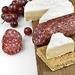 Brie Cheese And Salami On A Wooden Board stock photo