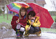 Brother & Sister In The Rain With Umbrellas stock photo